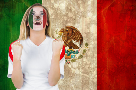 Excited mexico fan in face paint cheering against mexico flag in grunge effect photo