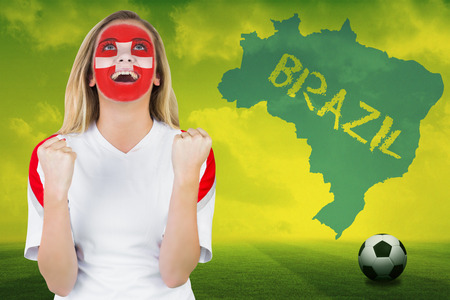 Excited fan in swiss face paint cheering against football pitch with brazil outline and text photo