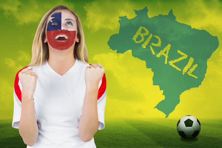 Excited chile fan in face paint cheering against football pitch with brazil outline and text photo