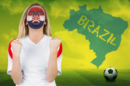 Excited croatia fan in face paint cheering against football pitch with brazil outline and text photo