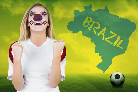 Excited south korea fan in face paint cheering against football pitch with brazil outline and text photo