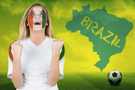 Excited ivory coast fan in face paint cheering against football pitch with brazil outline and text photo