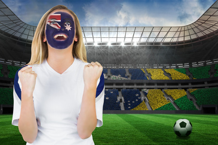 Excited australia fan in face paint cheering against large football stadium with brasilian fans photo
