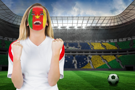 Excited cameroon fan in face paint cheering against large football stadium with brasilian fans photo