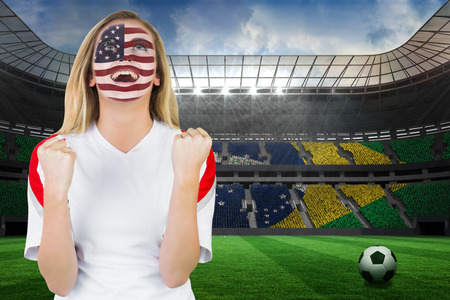 Excited fan in usa face paint cheering against large football stadium with brasilian fans photo