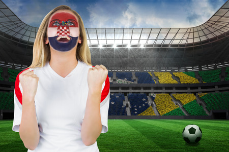Excited croatia fan in face paint cheering against large football stadium with brasilian fans photo