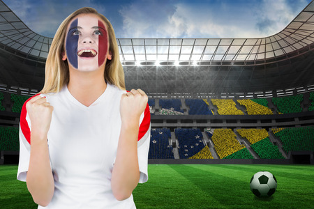 Excited france fan in face paint cheering against large football stadium with brasilian fans photo