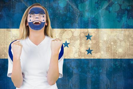 Excited honduras fan in face paint cheering against honduras flag in grunge effect photo