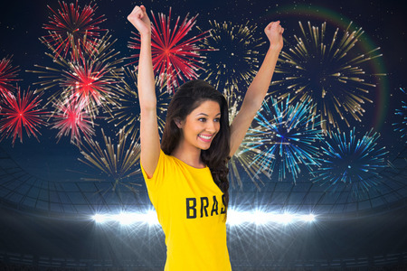 Excited football fan in brasil tshirt against fireworks exploding over football stadium photo