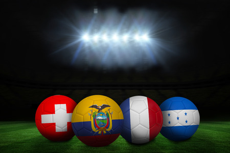 Group e footballs under spotlight on pitch photo