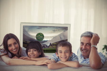 Family smiling at the camera with football showing on television at home on sofa photo