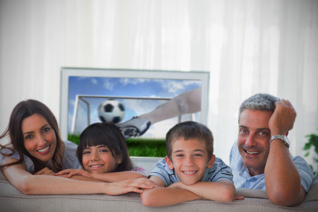 Family smiling at the camera with football showing on television photo