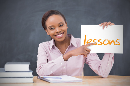 Happy teacher holding page showing lessons in her classroom at school photo