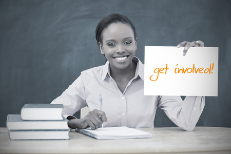 involved: Happy teacher holding page showing get involved in her classroom at school