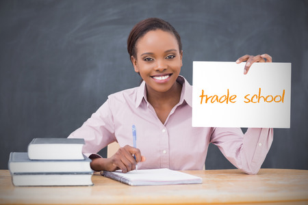 Happy teacher holding page showing trade school in her classroom at school photo