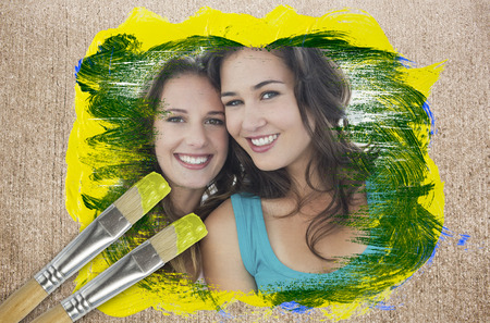 Composite image of friends smiling at camera with paintbrush dipped in yellow against weathered surface  photo