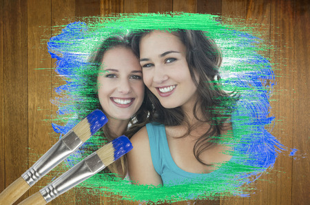 Composite image of friends smiling at camera with paintbrush dipped in blue against wooden surface with planks photo
