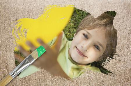 Composite image of little boy smiling at camera with paintbrush dipped in green against weathered surface  photo