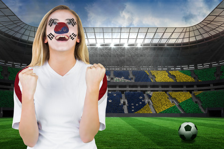 Excited south korea fan in face paint cheering against large football stadium with brasilian fans photo