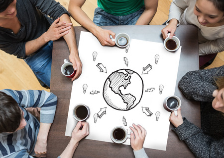 People sitting around table drinking coffee with page showing earth doodle with arrows photo