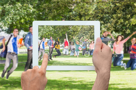 Hand holding tablet pc showing college students jumping in the park photo