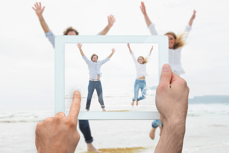 Hand holding tablet pc showing cheerful young couple jumping at beach photo