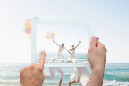 Hand holding tablet pc showing newlyweds having fun holding balloons photo