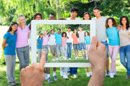 Hand holding tablet pc showing friends standing with arms around photo