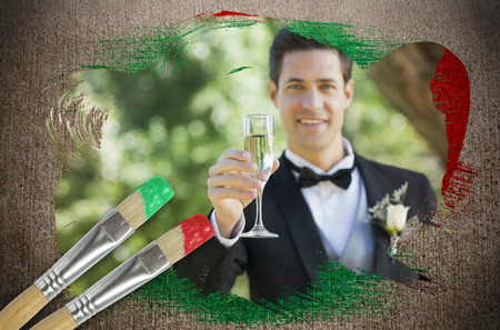 Composite image of groom toasting with champagne with paintbrush dipped in red against weathered surface  photo