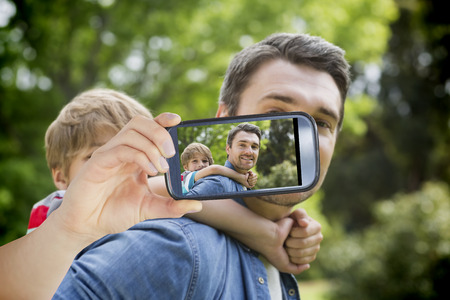 Hand holding smartphone showing father carrying young boy on back at park photo