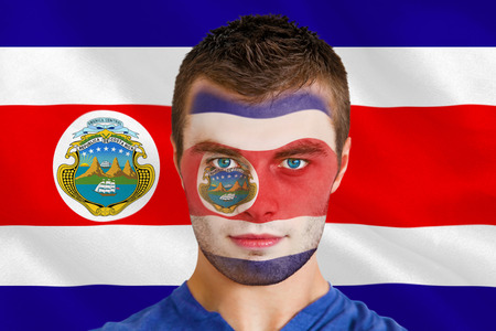 Composite image of serious young football fan in face paint against costa rica national flag photo