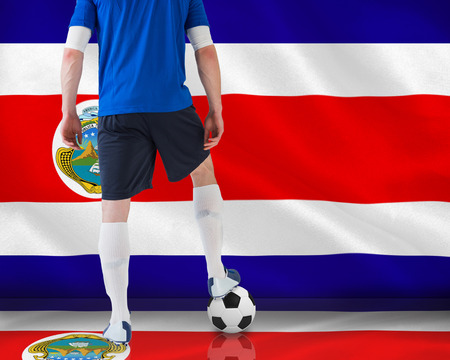 Handsome football player in blue jersey against costa rica national flag photo
