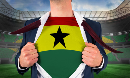 Businessman opening shirt to reveal ghana flag against large football stadium with brasilian fans photo