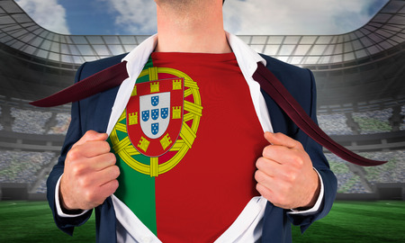 Businessman opening shirt to reveal portugal flag against large football stadium under spotlights photo