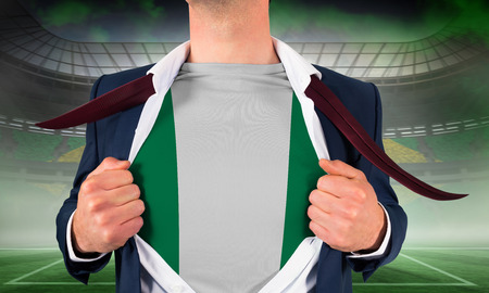 Businessman opening shirt to reveal nigeria flag against vast football stadium for world cup photo
