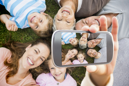 Hand holding smartphone showing extended family lying in circle at park photo