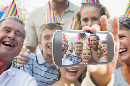 Hand holding smartphone showing happy extended family celebrating a birthday photo