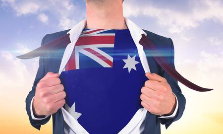 Businessman opening shirt to reveal australia flag against beautiful orange and blue sky photo
