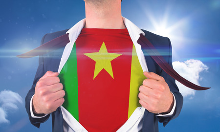 Businessman opening shirt to reveal cameroon flag against bright blue sky with clouds photo