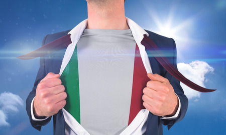 Businessman opening shirt to reveal italy flag against bright blue sky with clouds photo