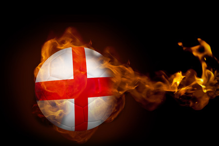 Composite image of fire surrounding england ball against black photo