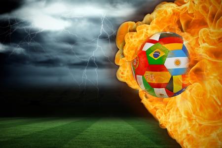 under fire: Imagen compuesta de fuego que rodea el f�tbol bandera internacional contra el campo de f�tbol bajo el cielo tormentoso