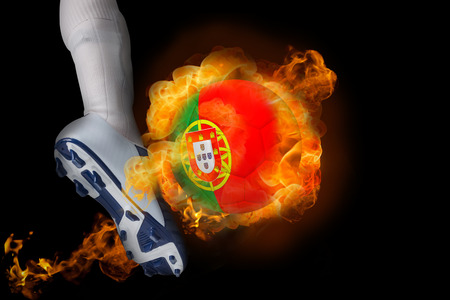 Football player kicking flaming portugal ball against black photo