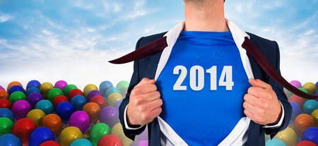 Businessman opening his shirt superhero style against many colourful balloons against sky photo