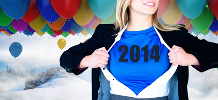 Businesswoman opening her shirt superhero style against many colourful balloons above snow photo