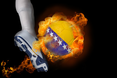 Football player kicking flaming bosnia ball against black photo