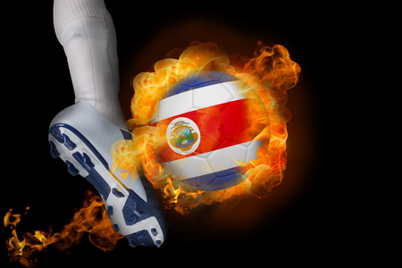 Football player kicking flaming costa rica ball against black photo