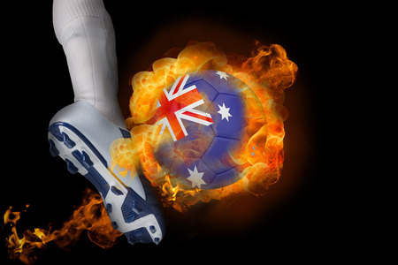 Football player kicking flaming australia ball against black photo