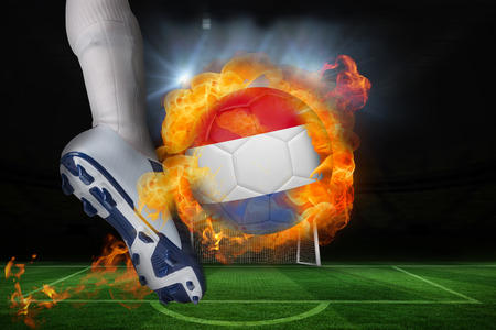 Football player kicking flaming netherlands flag ball against football pitch and goal under spotlights photo