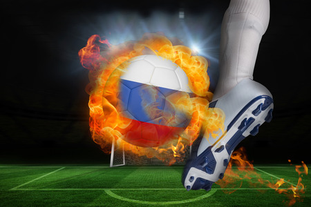 Football player kicking flaming russia flag ball against football pitch and goal under spotlights photo